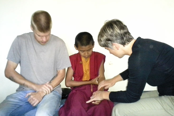 Volunteer nurse and Amy helping a monk